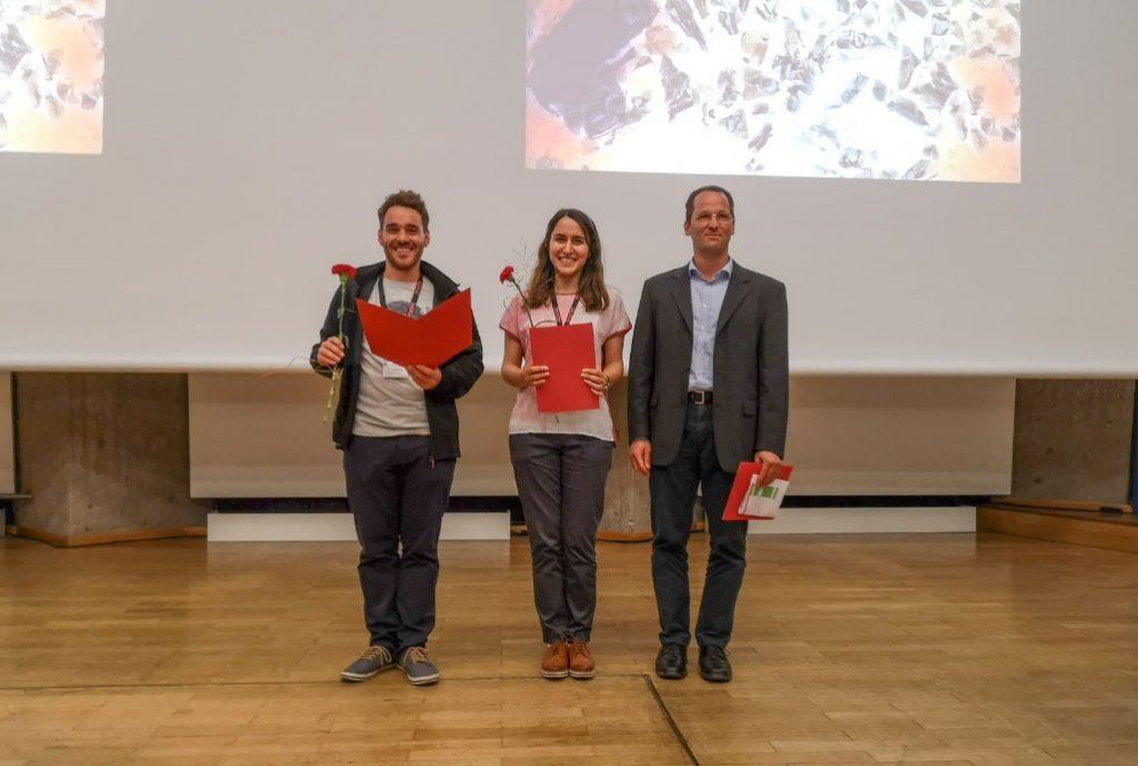 Drei Personen stehen nebeneinander, rechts und links je ein Mann, in der Mitte eine Frau. Die beiden links halten eine rote Mappe sowie je eine rote Rose in den Händen.