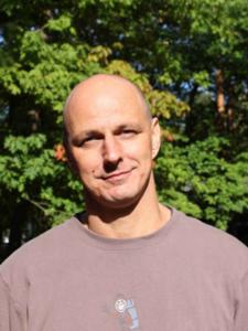ein Mann mit Glatze und einem blassrosa Hemd; im Hintergrund sind Bäume