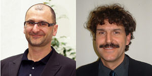 Porträts von zwei Männern. Der linke trägt einen schwarzen Anzug und hat sehr kurze Haare und eine Brille. Der rechte trägt ein schwarzes Hemd, hat krause dunkle Haare und einen Schnurrbart.